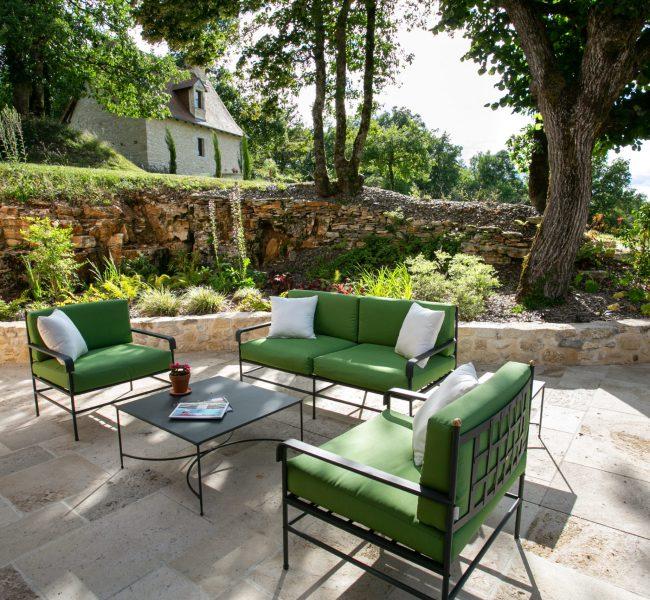 Coin détente sur une terrasse extérieure dallée, habillée d'une composition d'arbres et de fleurs avec un effet surélevée grâce a de la pierre.