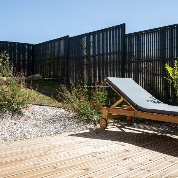 Espace détente sur une terrasse en bois au contour habillé de fleurs. Clôture design en métal gris.